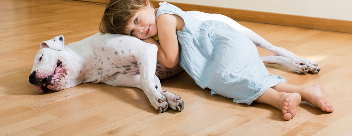 young girl and dog laying on wood floor
