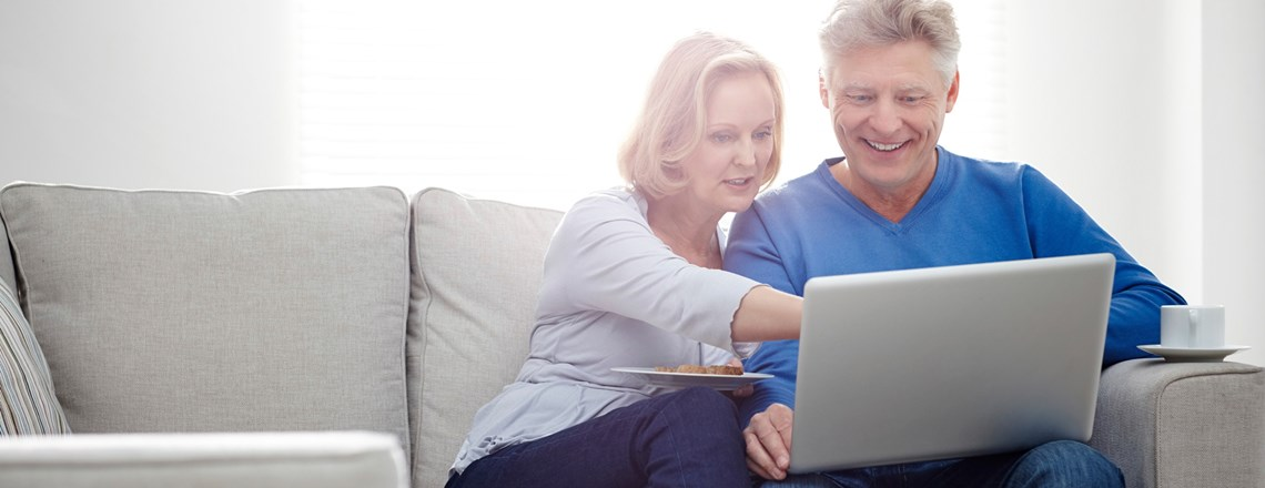 empty nester couple sitting on couch with laptop