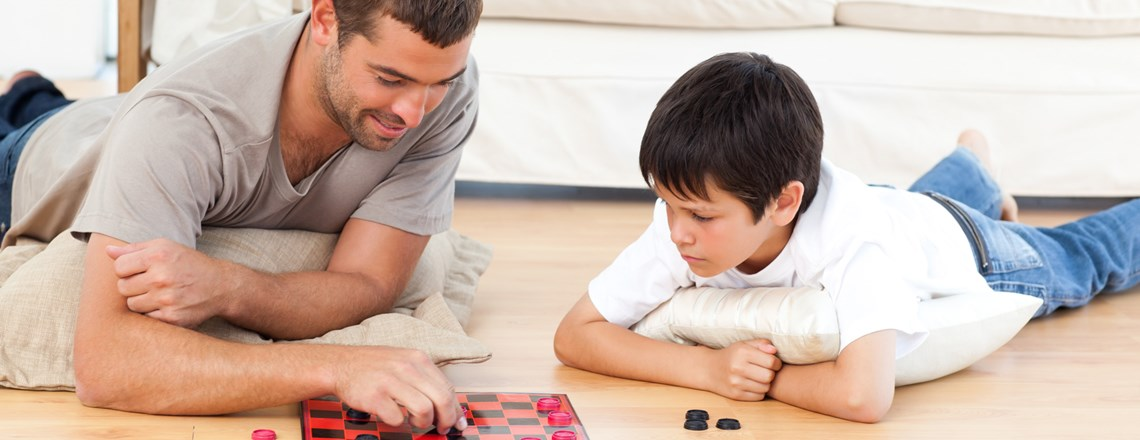 father and son playing checkers on laminate floor