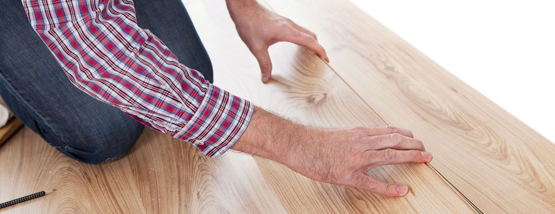contractor in plaid shirt installing laminate flooring