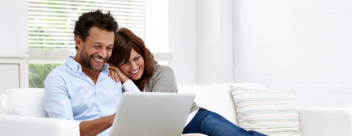 happy couple on couch with laptop