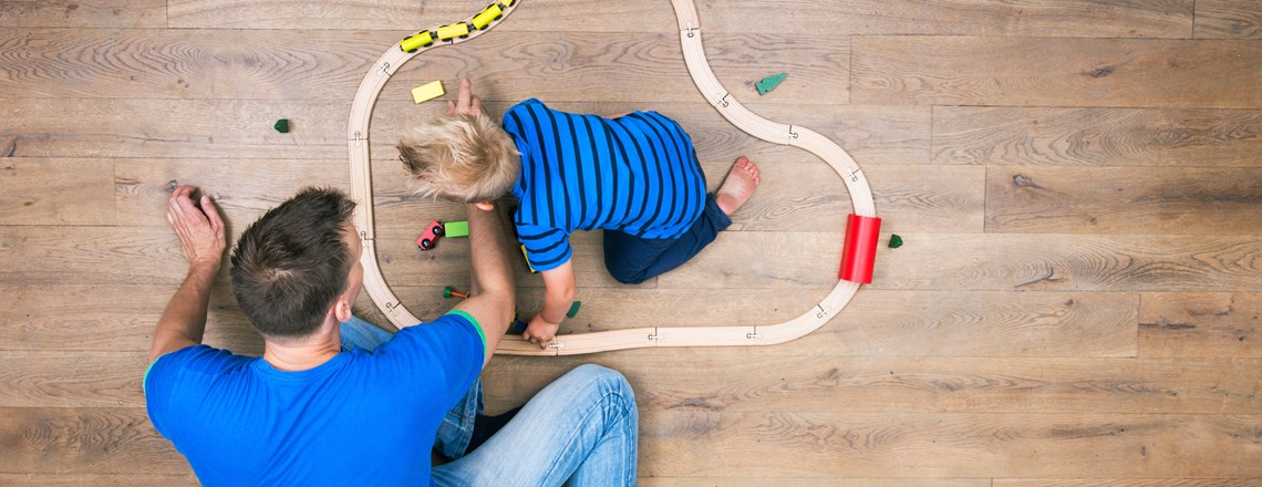 father and son playing with train on wood floor